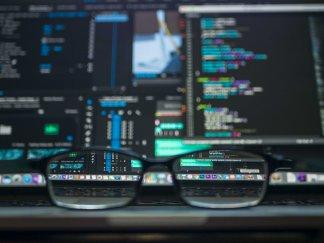 Glasses sitting in front of computer screens displaying code