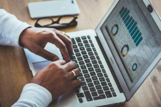 Man typing on a MacBook Air displaying various charts and summaries